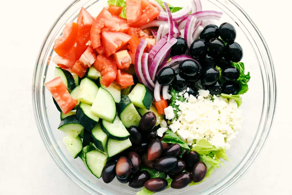Greek Salad ingredients in a clear bowl.