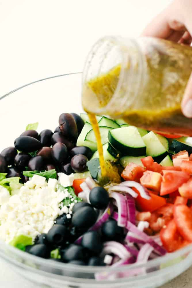 Greek Salad with olives, feta cheese, tomatoes and cucumbers with Greek Salad Dressing being poured over top.
