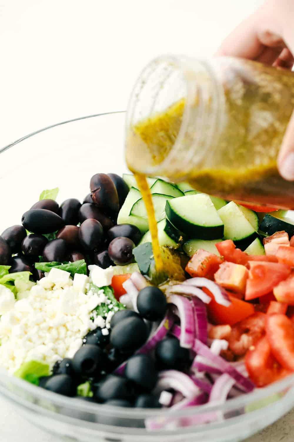 Pouring dressing on Greek salad ingredients.