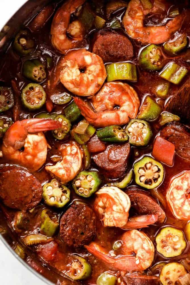 A stew of shrimp, okra, tomatoes, and sausage in a pot.