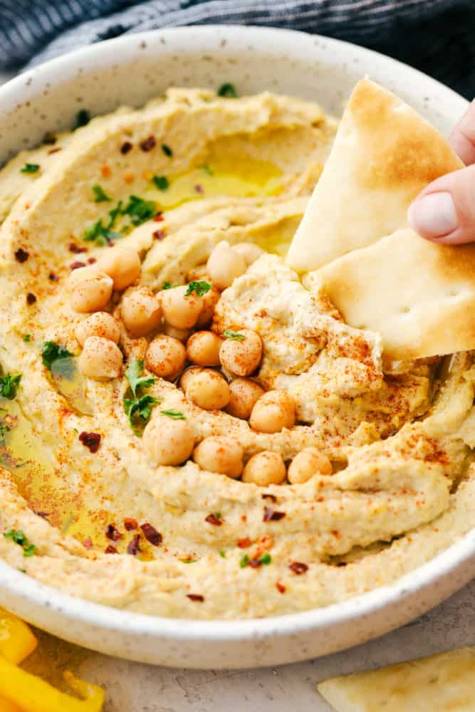 Hummus in a white bowl with a pita chip being dipped in it and chickpeas over top as a garnish.