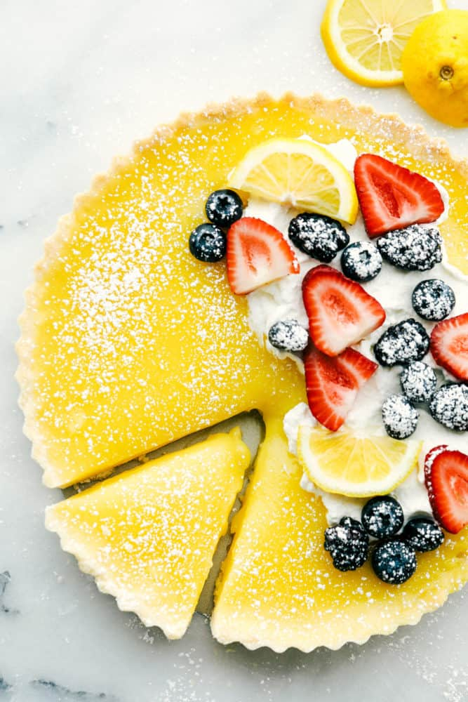 Lemon tart photo with fresh berries on top with lemon slices and powder sugar sprinkled on top and a slice cut out of the tart.