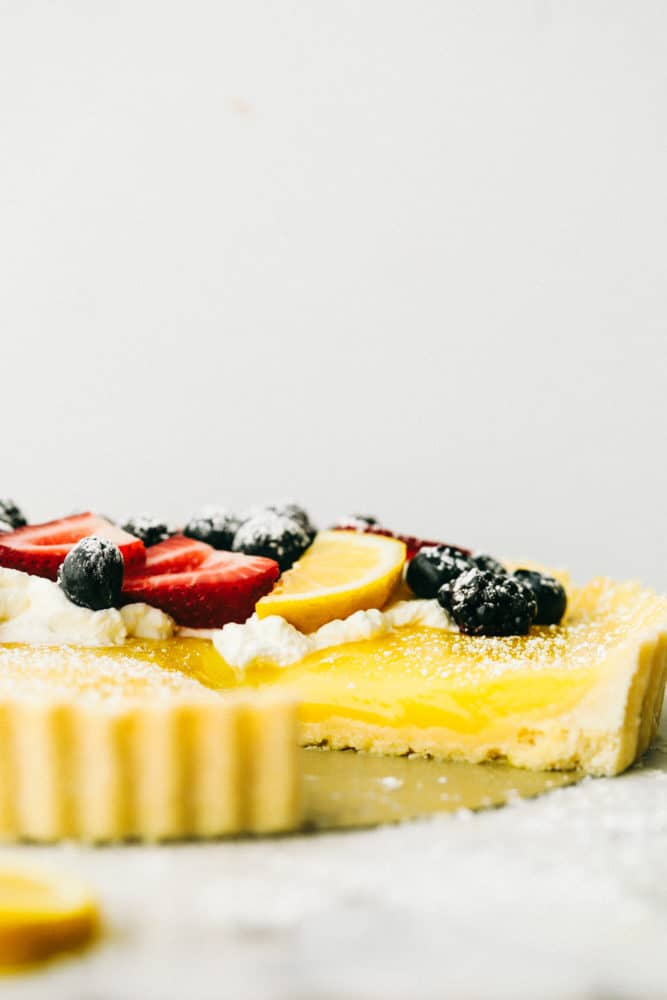 Lemon tart photo of a side of the dessert with fresh berries on top and powdered sugar.
