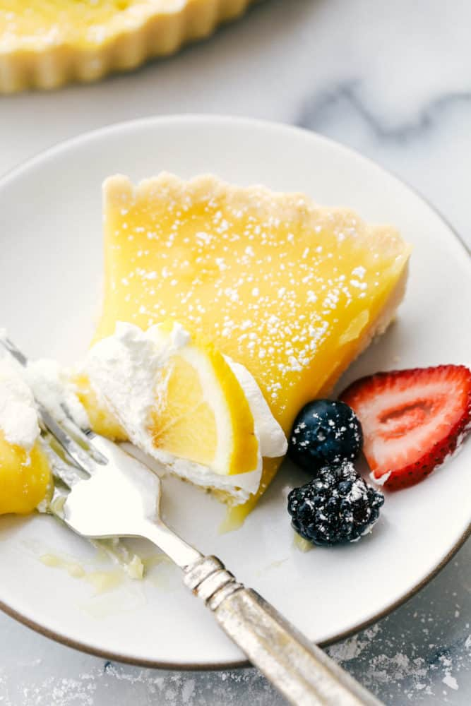 Lemon tart on a white plate with fresh berries on the side and a bite taken out of the tart.