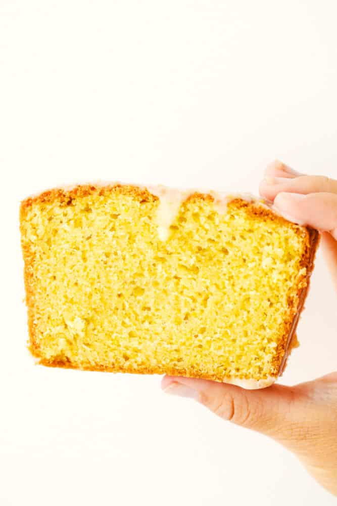 Slice of glazed lemon bread in a photo being held up by a hand.