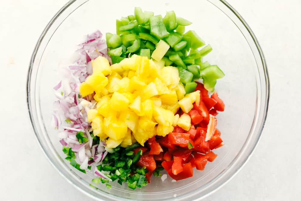 Ingredients for pineapple salsa in a clear bowl.