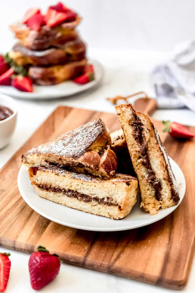 An image of nutella stuffed french toast sliced in half on a plate.