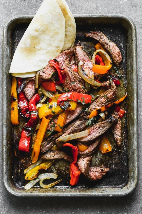 Grilled steak fajitas on a sheet pan with a tortilla on the side.