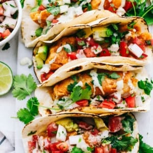 Baja fish tacos lined in a row.