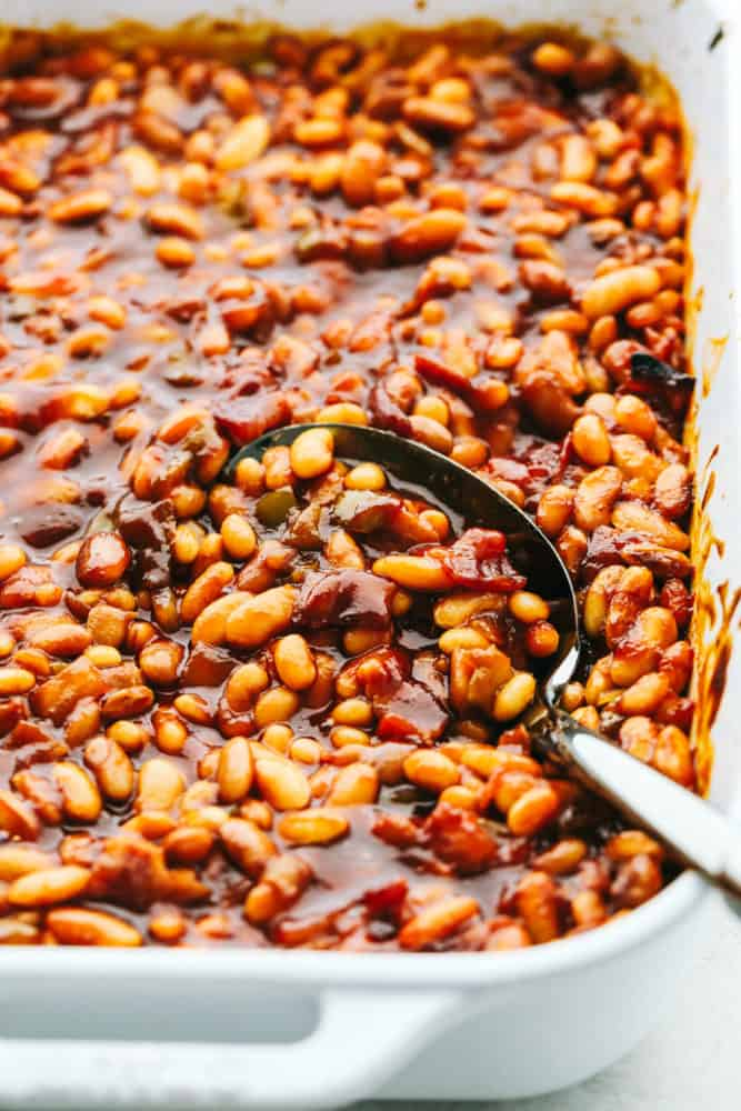 Scooping up baked beans with a serving spoon.