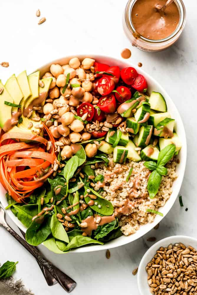 A large Buddha Bowl with spinach, quinoa, carrots, cucumbers, tomatoes, chickpeas, and avocado with a jar or dark creamy dressing to the side.