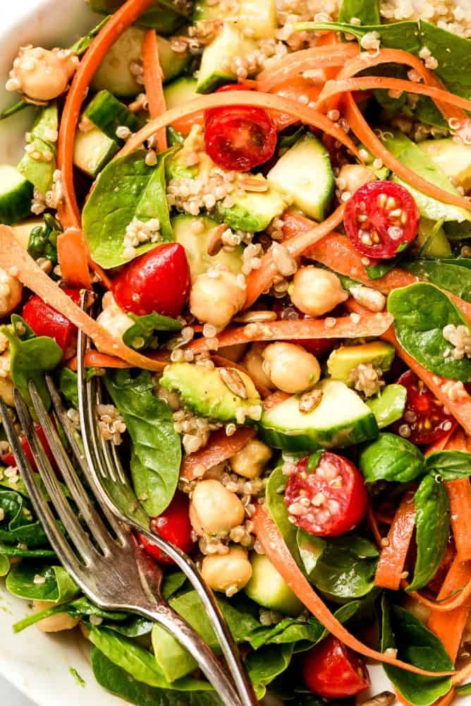 A salad of spinach, cucumbers, grape tomatoes, carrot ribbons, avocado, chickpeas, and quinoa all mixed together.