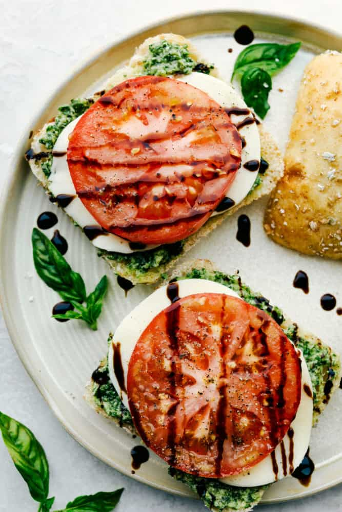 Balsamic glaze drizzled over caprese sandwiches on a plate.