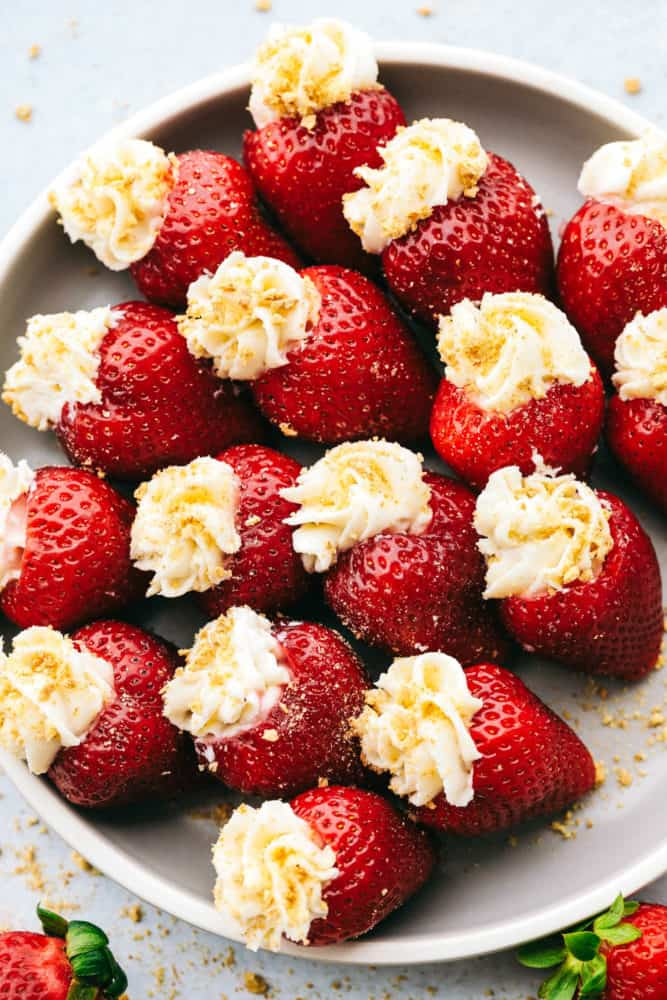 A plate filled with cheesecake stuffed strawberries.