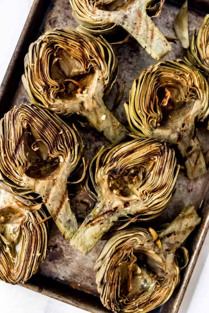 Grilled artichokes on a baking sheet.