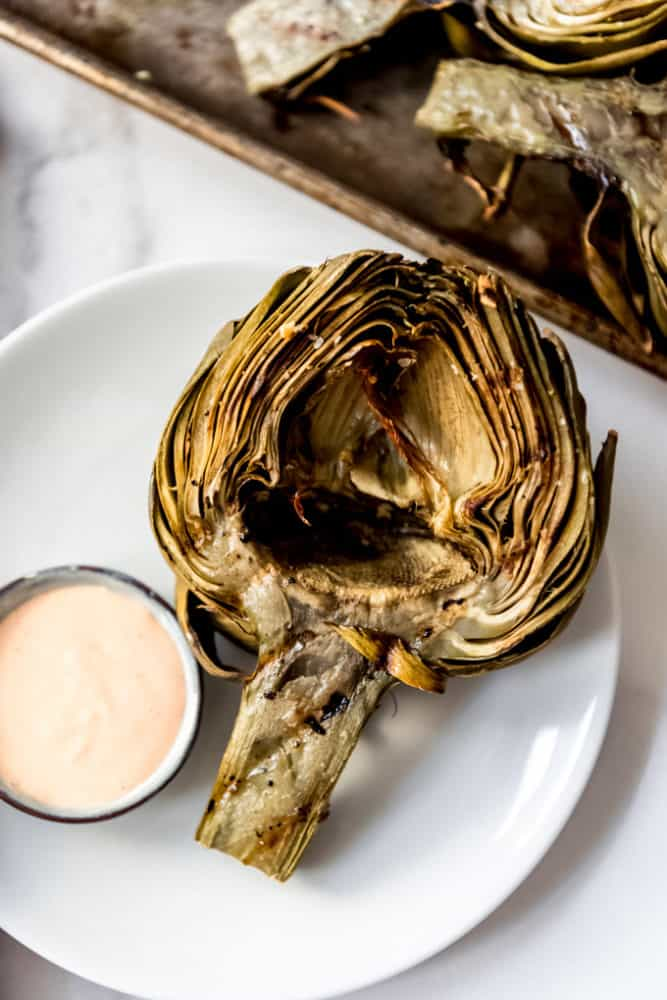 A grilled artichoke half on a white plate with dipping sauce.
