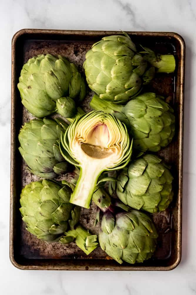 Artichoke halves on a baking sheet.