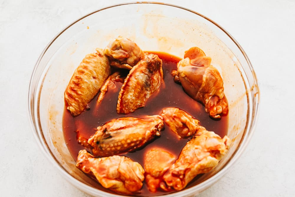 Marinating chicken wings in a clear bowl.