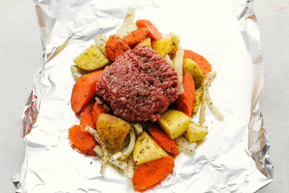 Foil packet with carrots, potatoes and a hamburger patty.