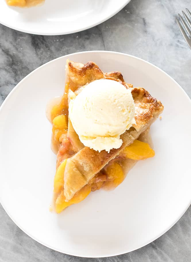 A slice of peach pie on a white plate with a scoop of vanilla ice cream on top.