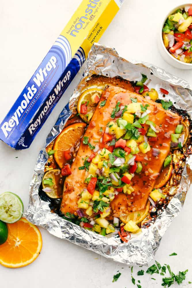 Grilled salmon in Reynolds wrap foil with mango salsa over top with oranges and lime slices.