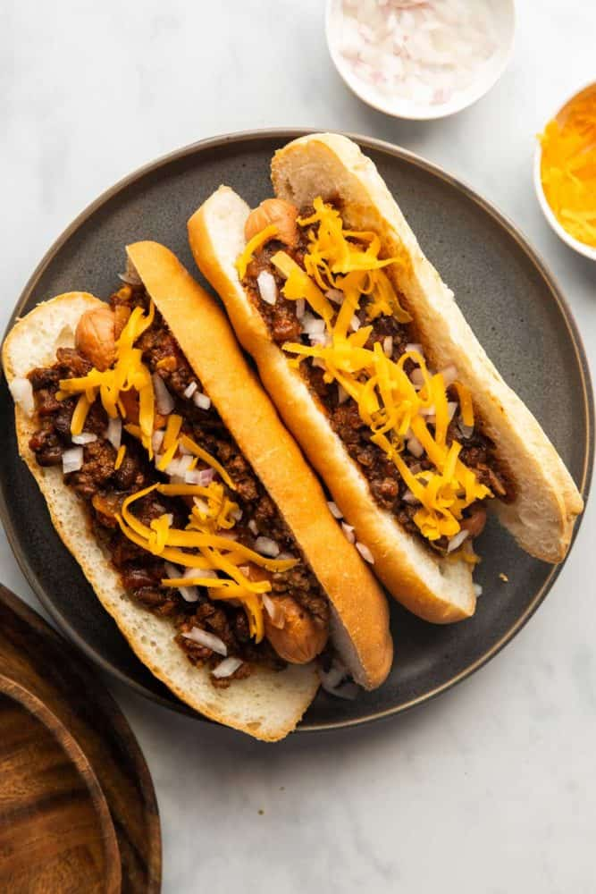 Chili Dogs served on a plate with shredded cheddar and onions on the side