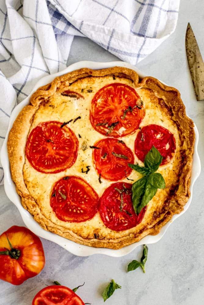 Tarte aux tomates dans un plat à tarte blanc avec du basilic frais sur le dessus
