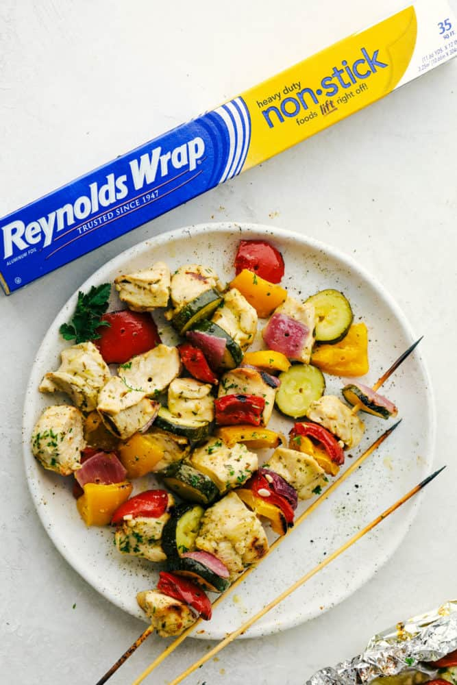 Chicken and vegetables on a white plate with Reynolds wrap box on the side.