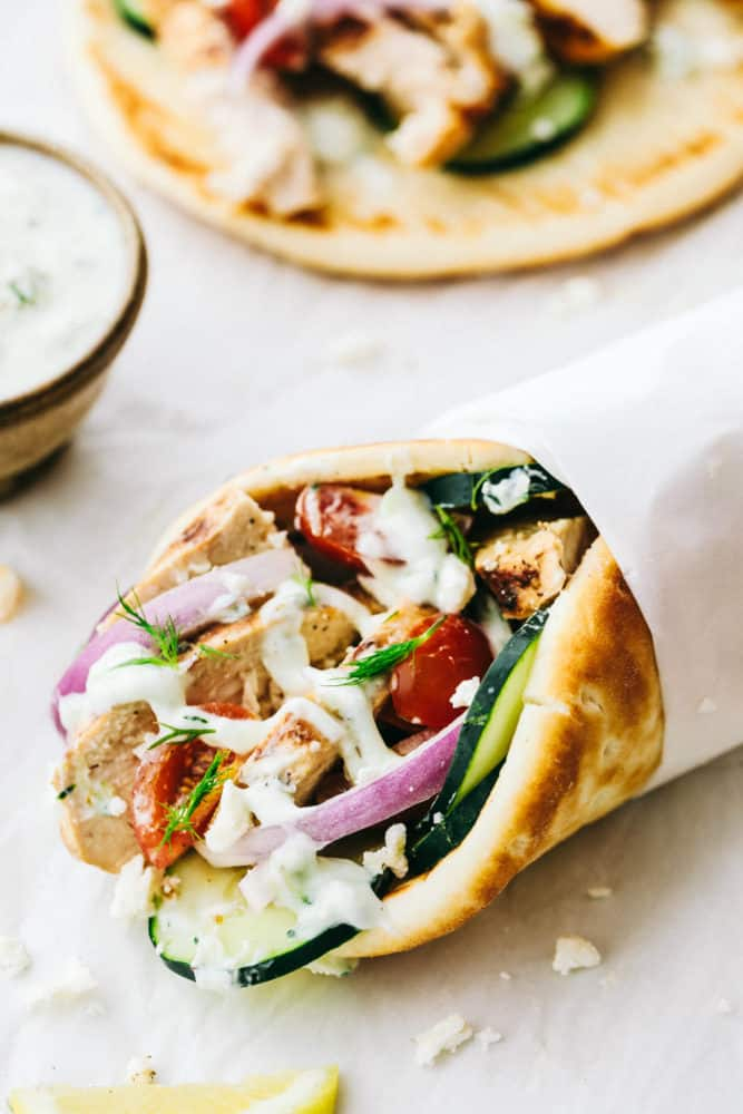 Homemade chicken gyro with tzatziki wrapped up in parchment paper.