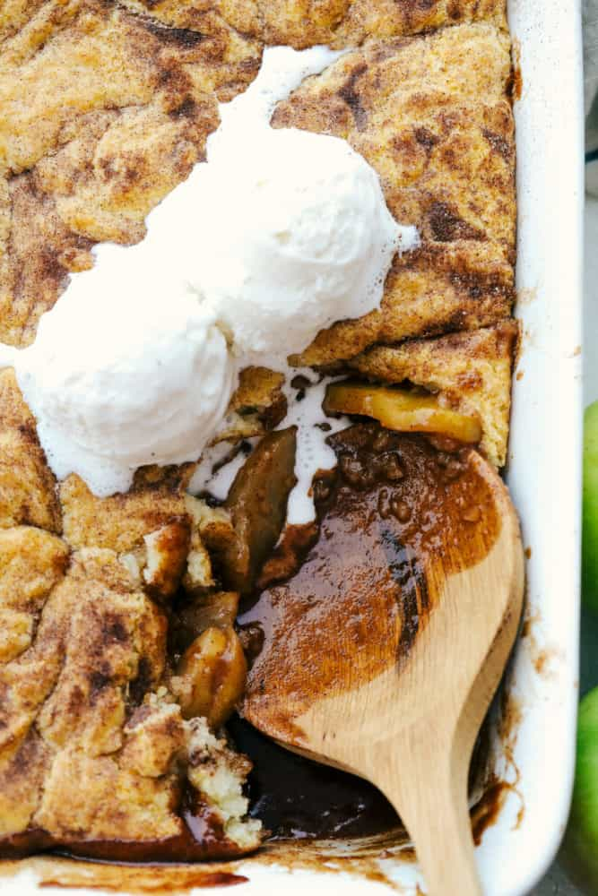 Scooping apple cobbler and vanilla ice cream out of a white baking dish.