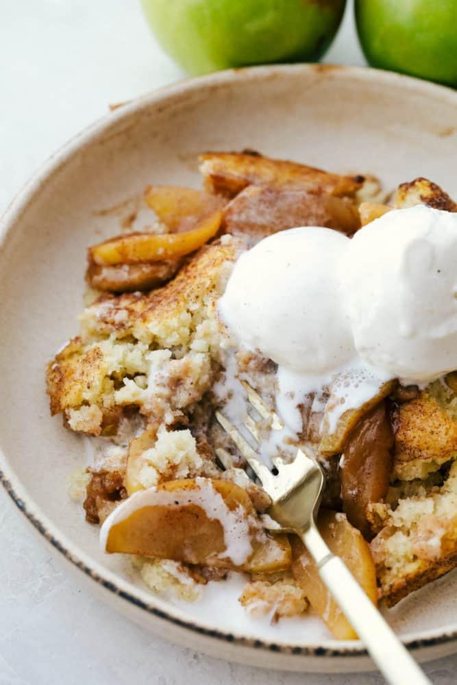 Sapateiro de maçã em um prato coberto com sorvete de baunilha.