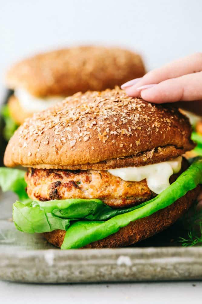 Close-up em pegar um hambúrguer de salmão acabado.