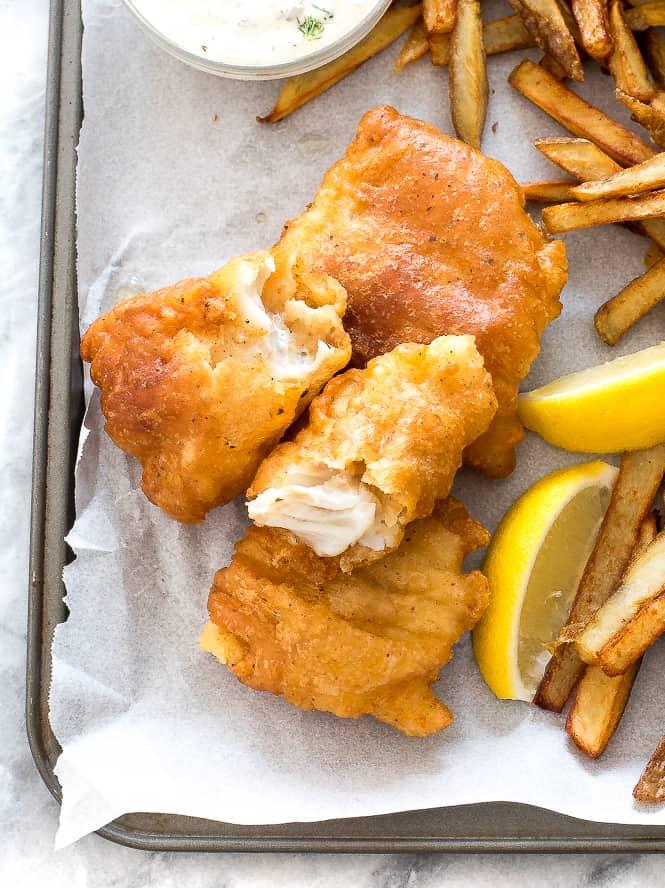 Fish and chips sur une plaque avec du papier sulfurisé sur le dessus avec des frites et des tranches de citron sur le côté.