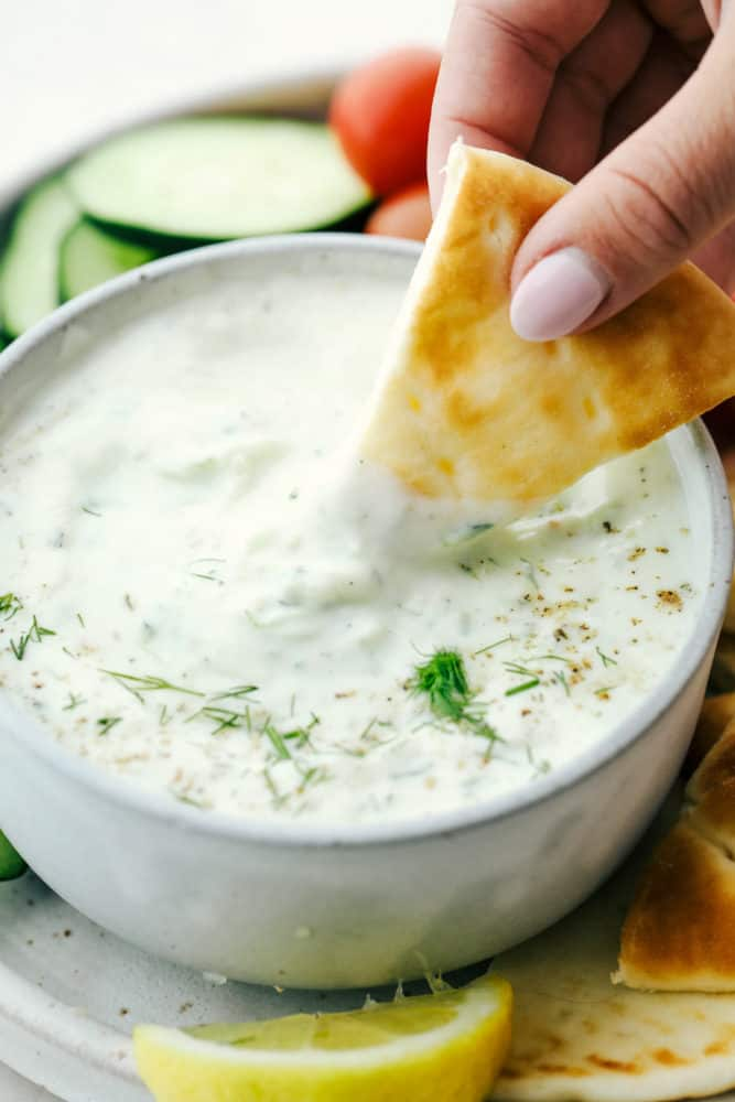 Dipping a chip in Tzatziki sauce.
