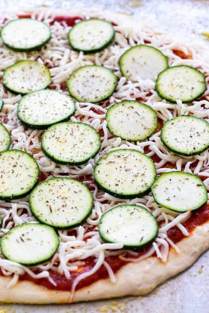 Thin slices of zucchini layered on top of a pizza