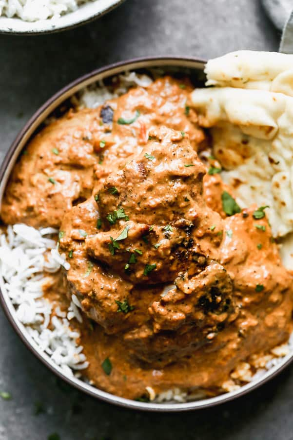 Butter chicken in a bowl covering white rice with naan bread on the side.