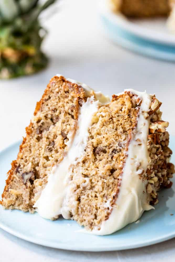 A slice of hummingbird cake laying on its side on a blue plate.