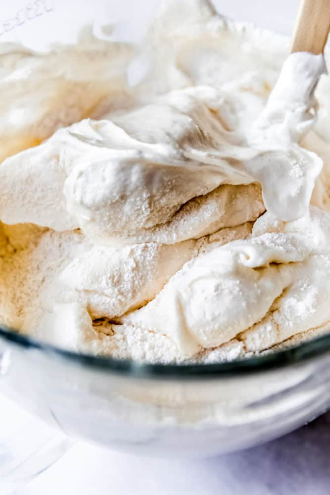 Folding sifted flour and sugar into egg whites that have been whipped into soft peaks.