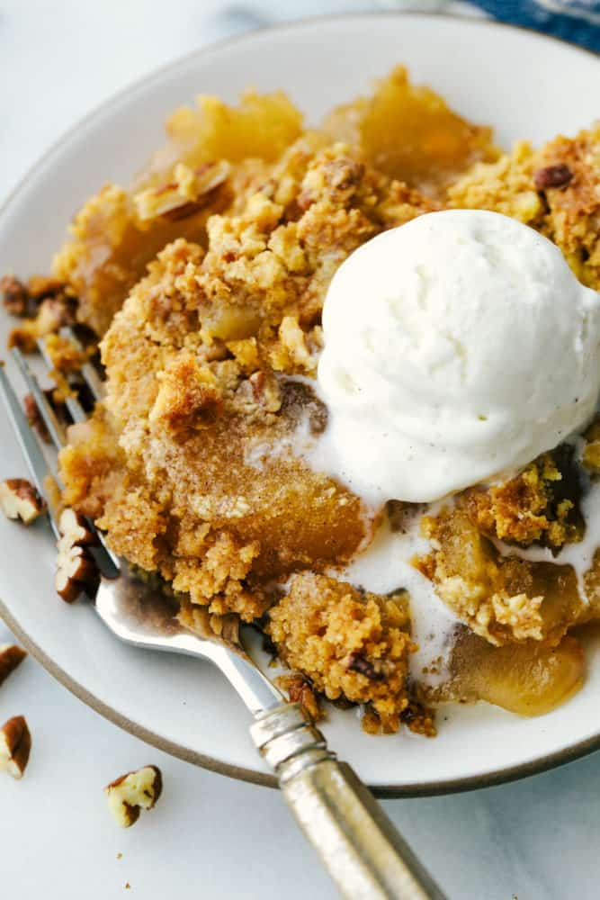 Apple dump cake on a white plate with a fork on the side. Topped with ice cream.