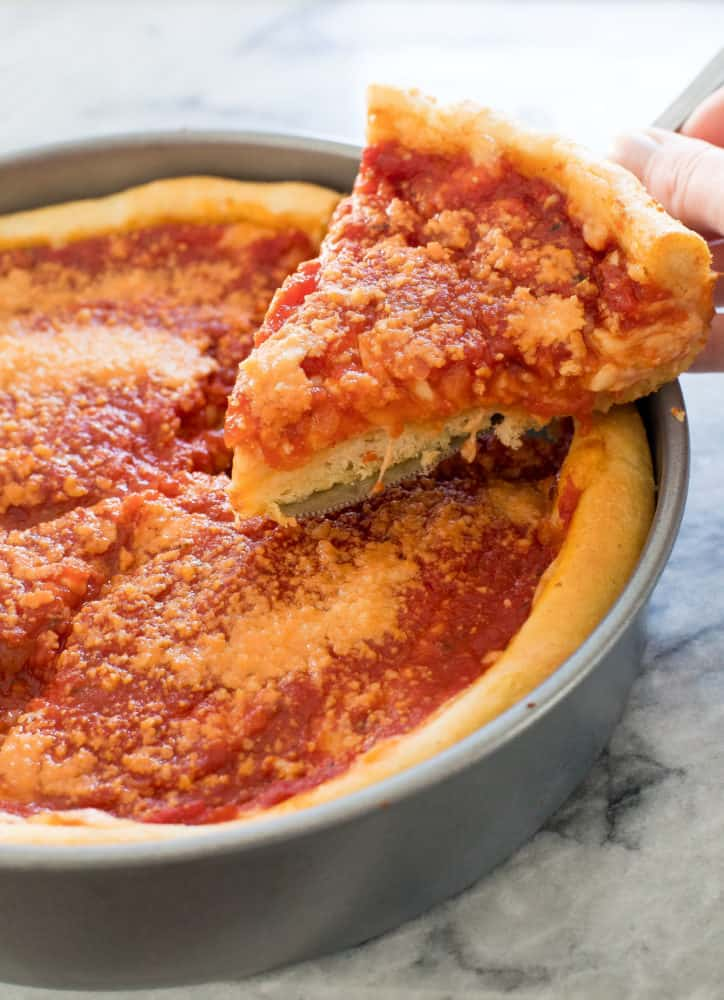 Deep dish pizza in a pan with a slice getting taken out.
