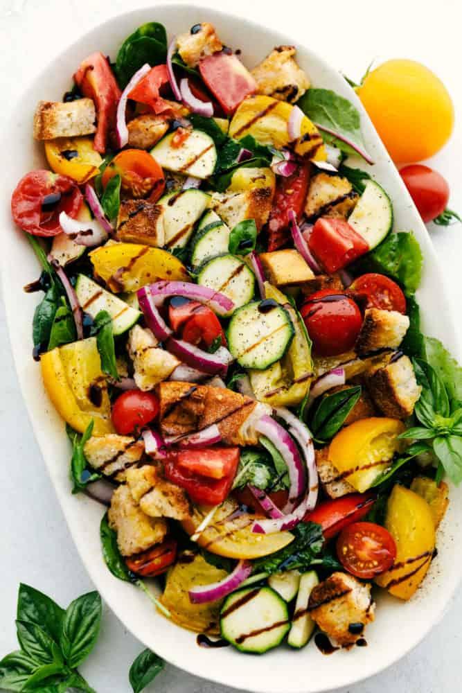 Salada Panzanella em um prato branco com folhas de hortelã ao redor e tomates.
