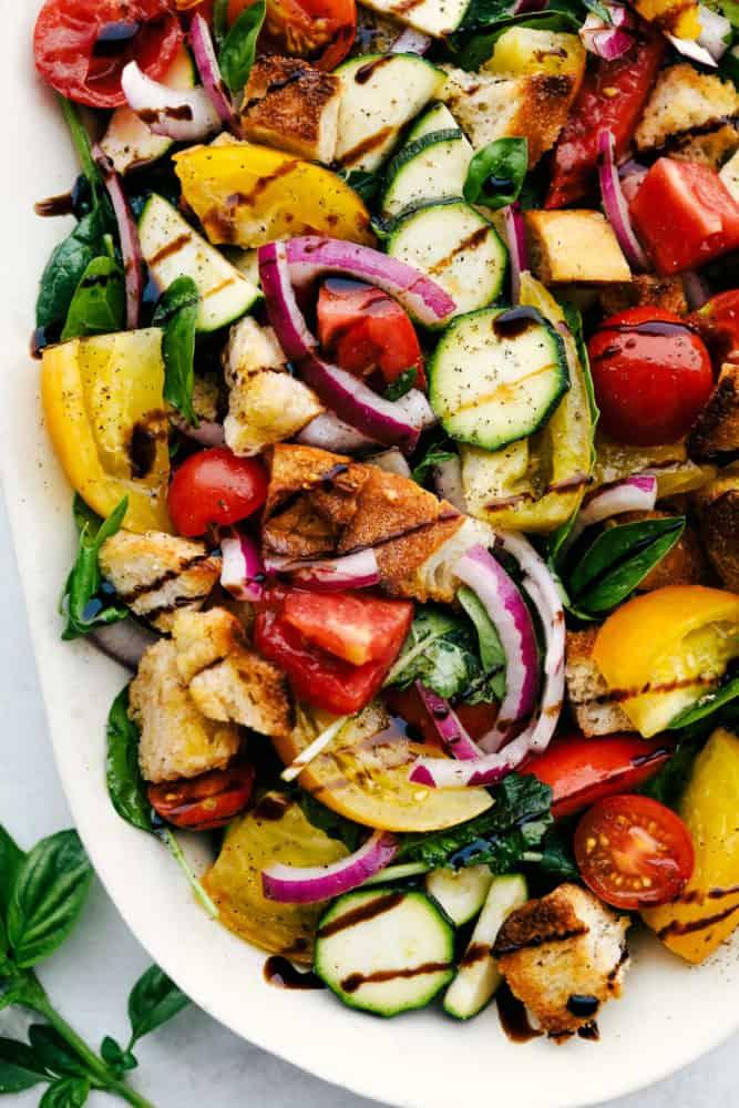 Uma foto de perto de Salada Panzanella em um prato branco.