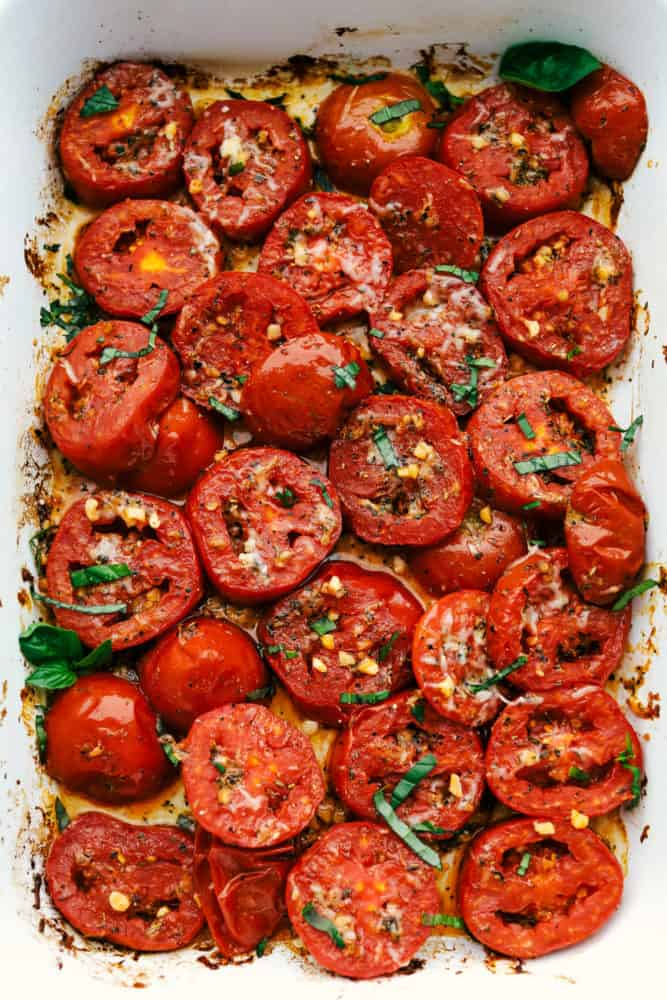 Roasted tomatoes sliced in a pan topped with basil and cheese