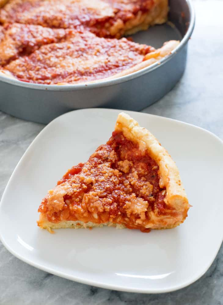 A slice of deep dish pizza sitting on a white plate.