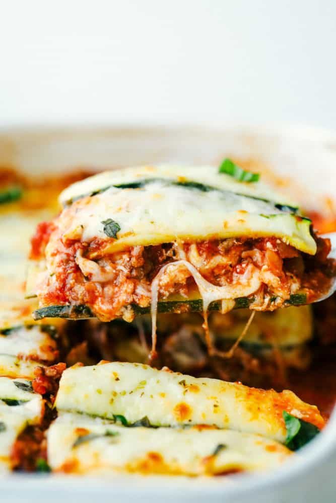 A photo of zucchini lasagna having a piece taken out of the casserole dish.