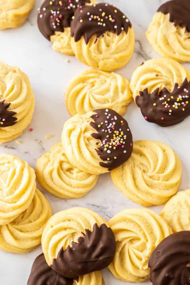 Un lot de biscuits au beurre, certains enrobés de chocolat, répartis sur un plan de travail en marbre