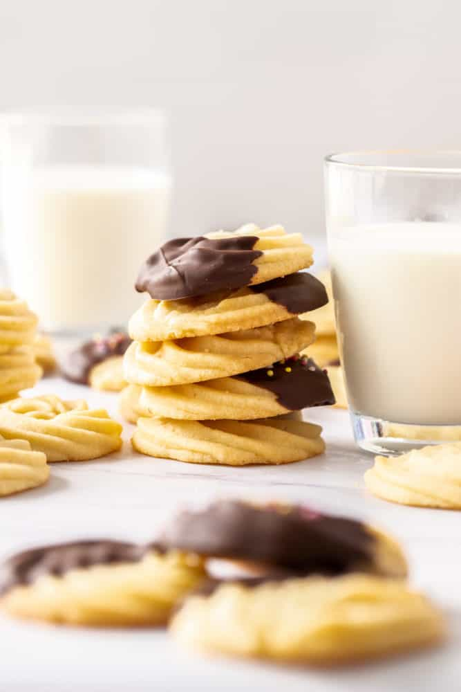 A stack of butter cookies, some chocolate coated, sitting next to a glass of milk