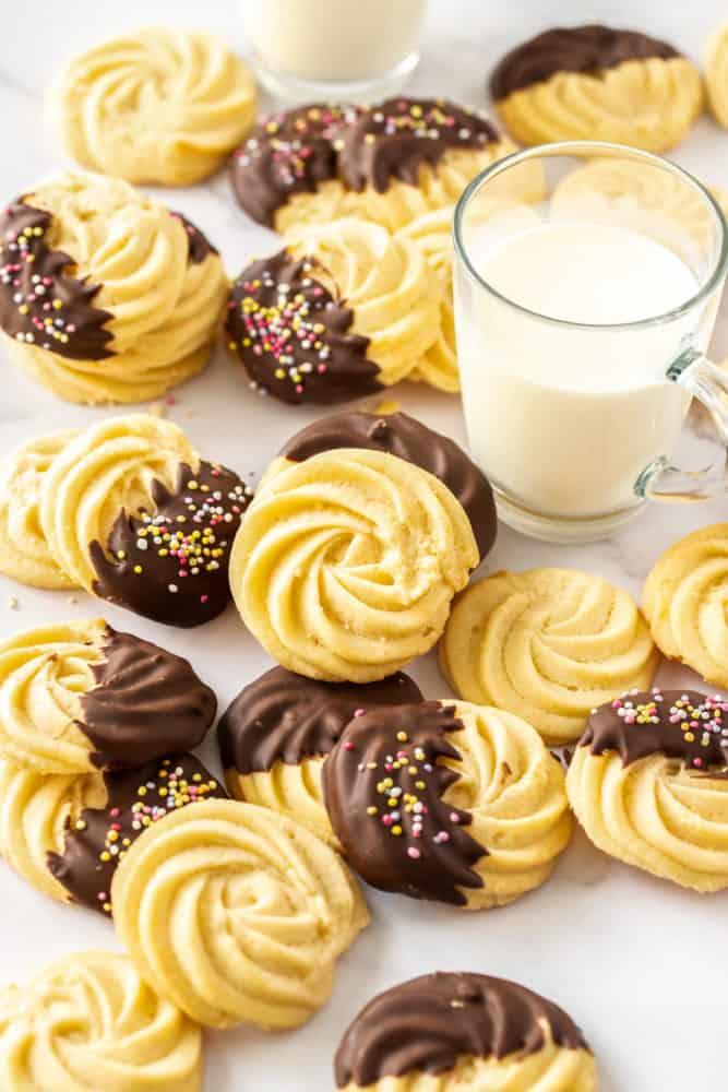 Un lot de biscuits au beurre, certains enrobés de chocolat, à côté d'un verre de lait
