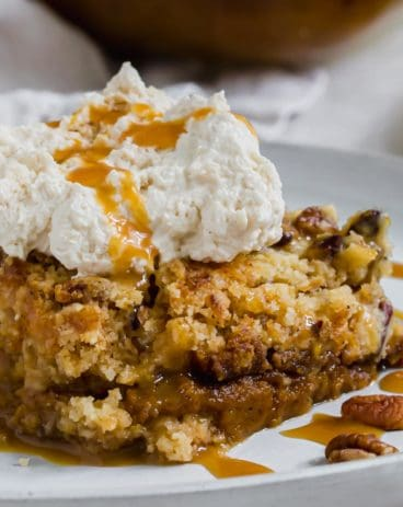Slice of pumpkin dump cake with whipped cream and caramel sauce drizzled on top.