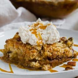Pumpkin dump cake topped with whipped cream and caramel sauce.